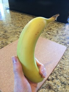 Grasp the banana firmly with your non-writing hand